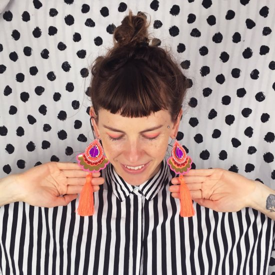 dakota rae dust designer bec denton wearing a monochrome striped shirt against a black and white polka dot wall, wearing fluorescent statement tassel earrings
