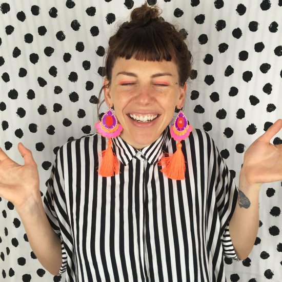 dakota rae dust designer bec denton wearing a monochrome striped shirt and orange and pink statement tassel earrings against a black and white polka dot wall