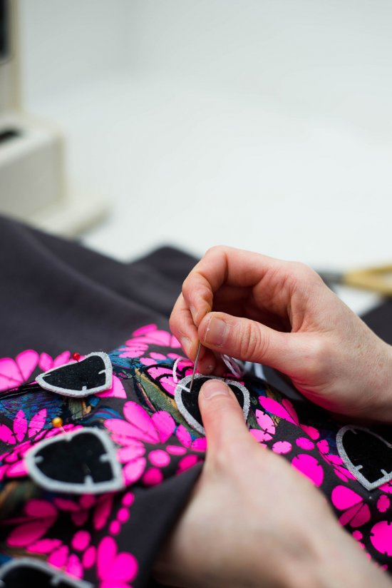 Bec Denton's hands, stitching an embellished sweatshirt. Grey with a neon pink print