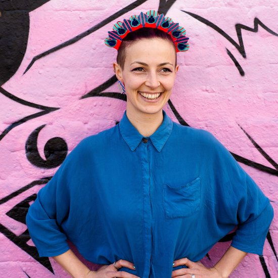 A white woman standing with her hands on her hips staring beyond the camera. She wears a colourful halo style, graphic stripe festival headdress and a blue shirt in front of a wall covered in pink graffiti