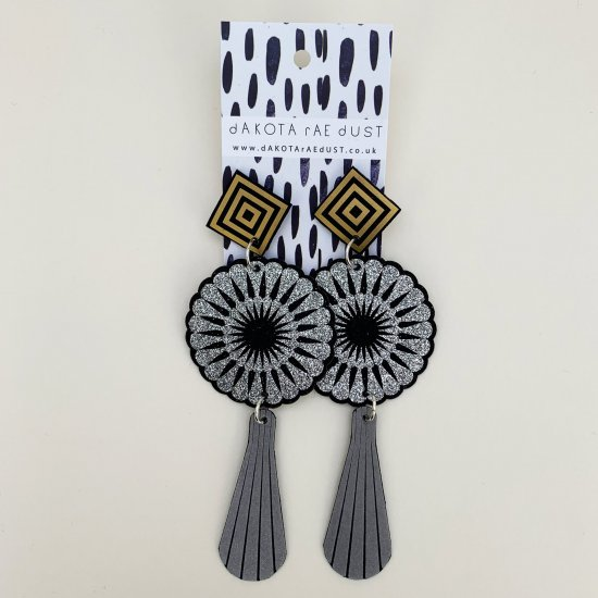 A pair of extra long art deco earrings featuring black and silver circular motifs and elongated grey teardrops suspended below black and gold square studs are seen against an off white background