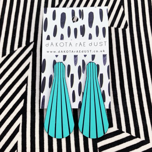 Turquoise stud earrings on a stripey background