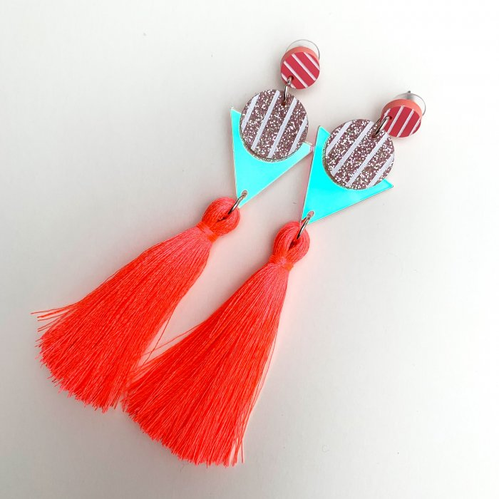 product shot of neon coral tassel earrings