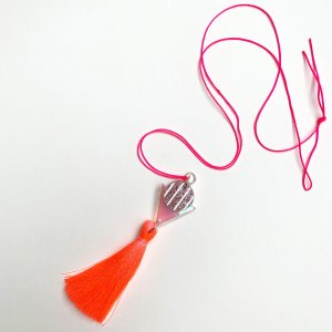 product shot of neon coral tassel pendant