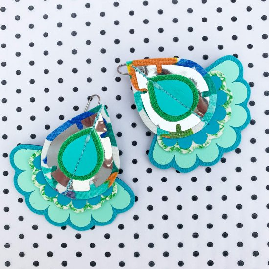 A pair of green oversize statement earrings are seen on a white background with small black polka dots. The earrings are made from large teardrop shape components with two scallop edged shapes sitting underneath.