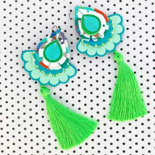 Fluorescent green, statement tassel earrings on a polka dot background