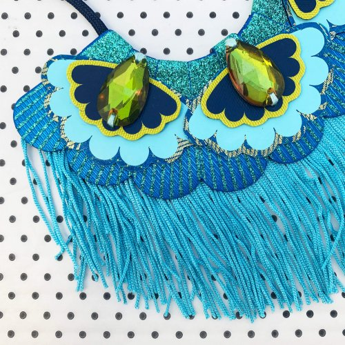 Close up of the turquoise fringe, bib necklace showing green jewels and scalloped edges