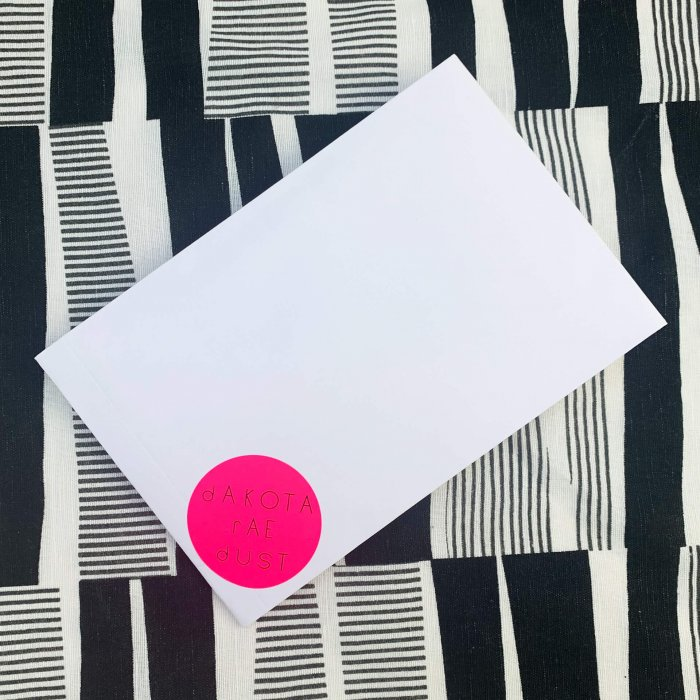 dakota rae dust gift voucher seen in a white envelope against a black and white boldly patterned background