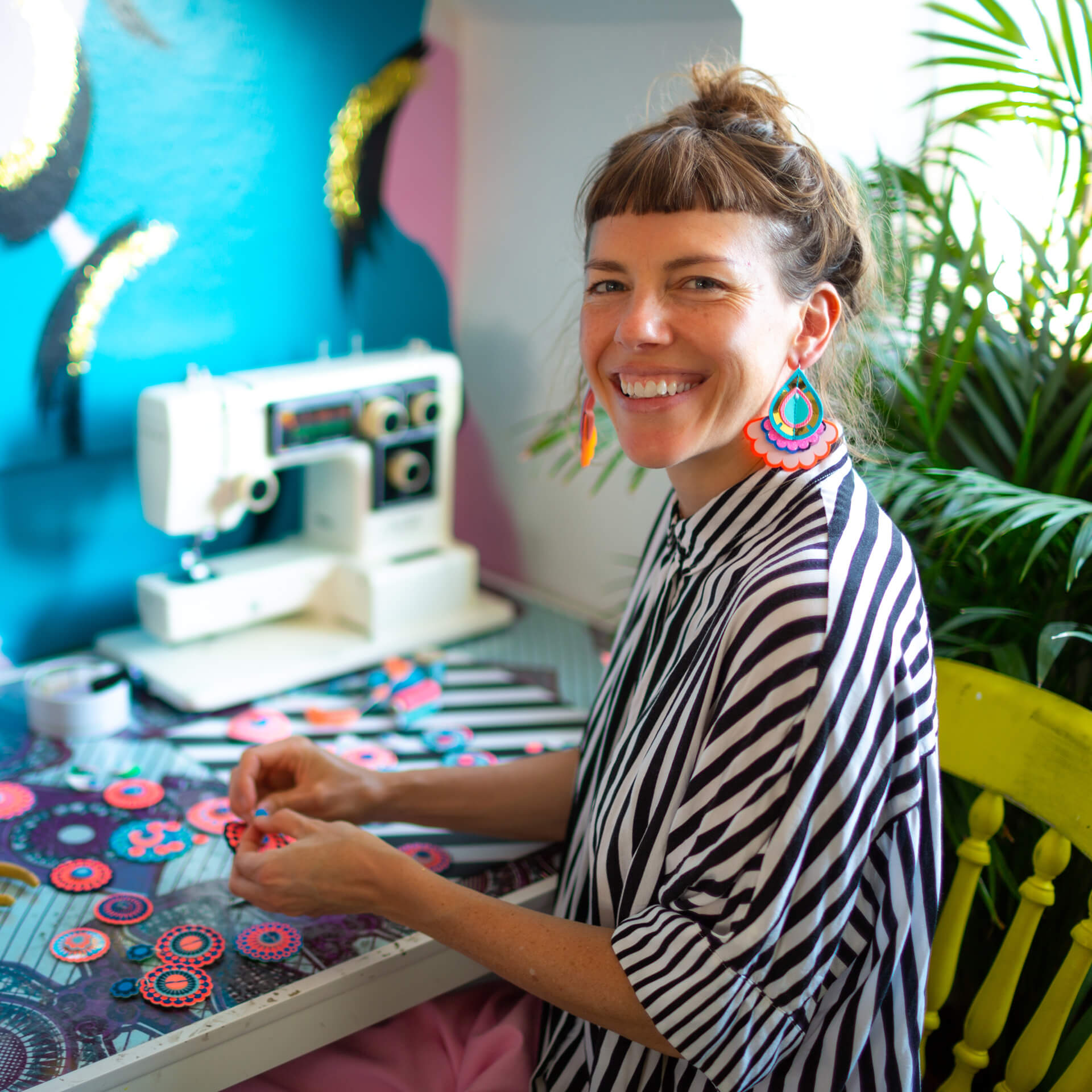 designer bec sitting at her desk with her sewing machine