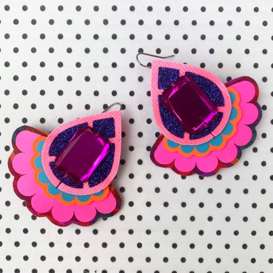 A pair of tear drop shape fluorescent pink, royal blue and purple Oversize statement earrings against a black and white polka dot background.