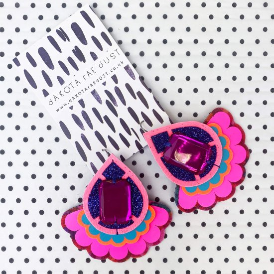 A pair of teardrop shape, fluorescent pink, royal blue and purple oversize statement earrings, displayed on a black and white patterned, branded card, against a white background with tiny black dots.