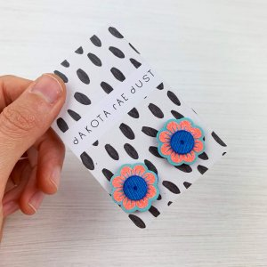 Floral stud earrings held close to the camera on a monochrome patterned backing card