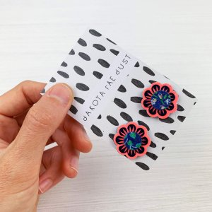 neon coral and navy floral stud earrings on a monochrome patterned backing card