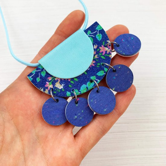 Jangly charm necklace held close to the camera, showing the recycled fabric reverse side