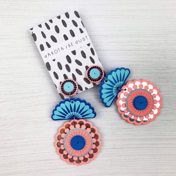 A pair of Statement stud circle arch earrings cut from peach and turquoise fabric and printed with silver detail are displayed on a black and white patterned dakota rae dust branded card are lying on an off white background.
