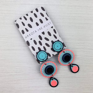 Dangly charm earrings in coral and blue displayed on a monochrome patterned backing card