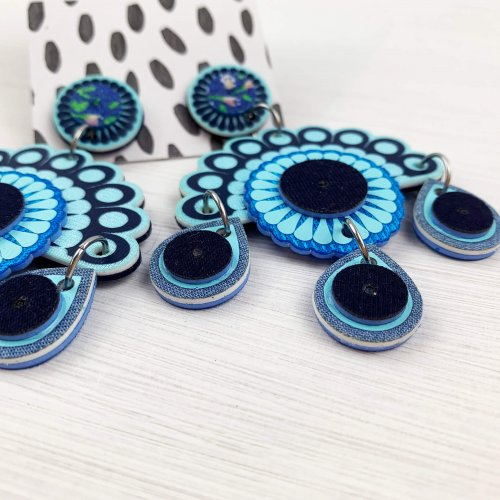 Statement earrings cut from blue fabric, seen from the side to show depth of material