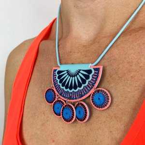 Neon coral and blue, jangly charm necklace worn by a model in a bright neon red vest