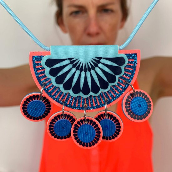 Designer Bec holds a jangly charm necklace close to the camera to show detail.