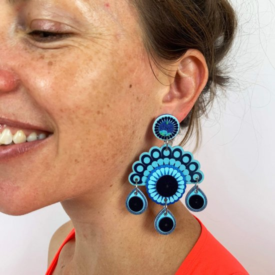 Chandelier style statement earrings worn by a smiling model