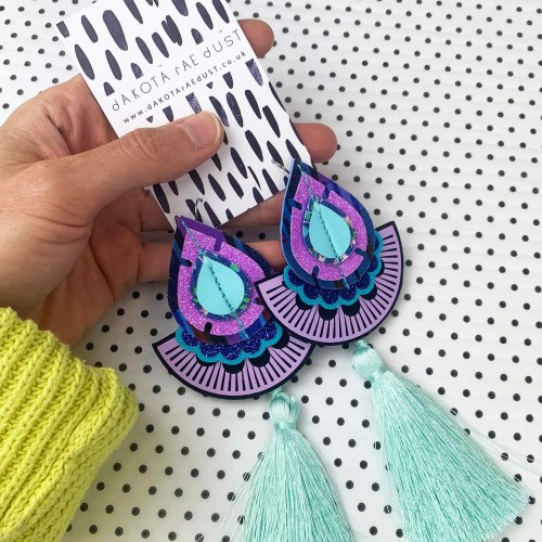 Turquoise and lilac statement tassel earrings held in a hand, the bright yellow wooly sleeve is visible in the corner of the image