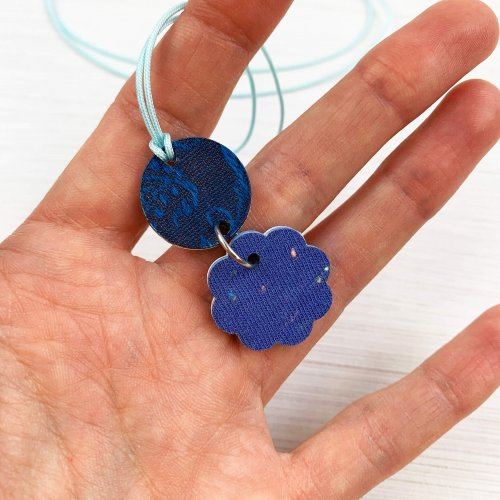 Close up of the reverse side of a charm pendant necklace showing the blue fabric back