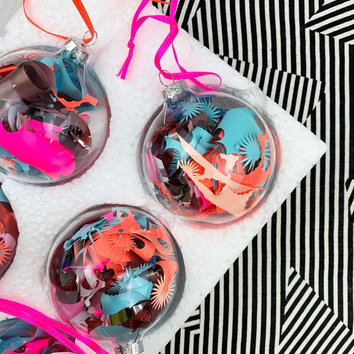 a set of five pink peach blue baubles against a black and white stripey background