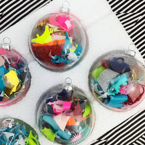 a tray of colourful Christmas baubles filled with fluorescent vinyl waste on a black and white striped backdrop
