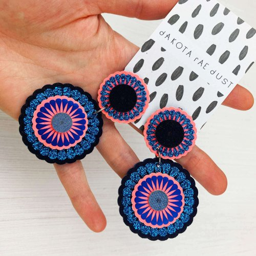 Glittery blue and pink decorative disc statement earrings held in a woman's hand against a white background