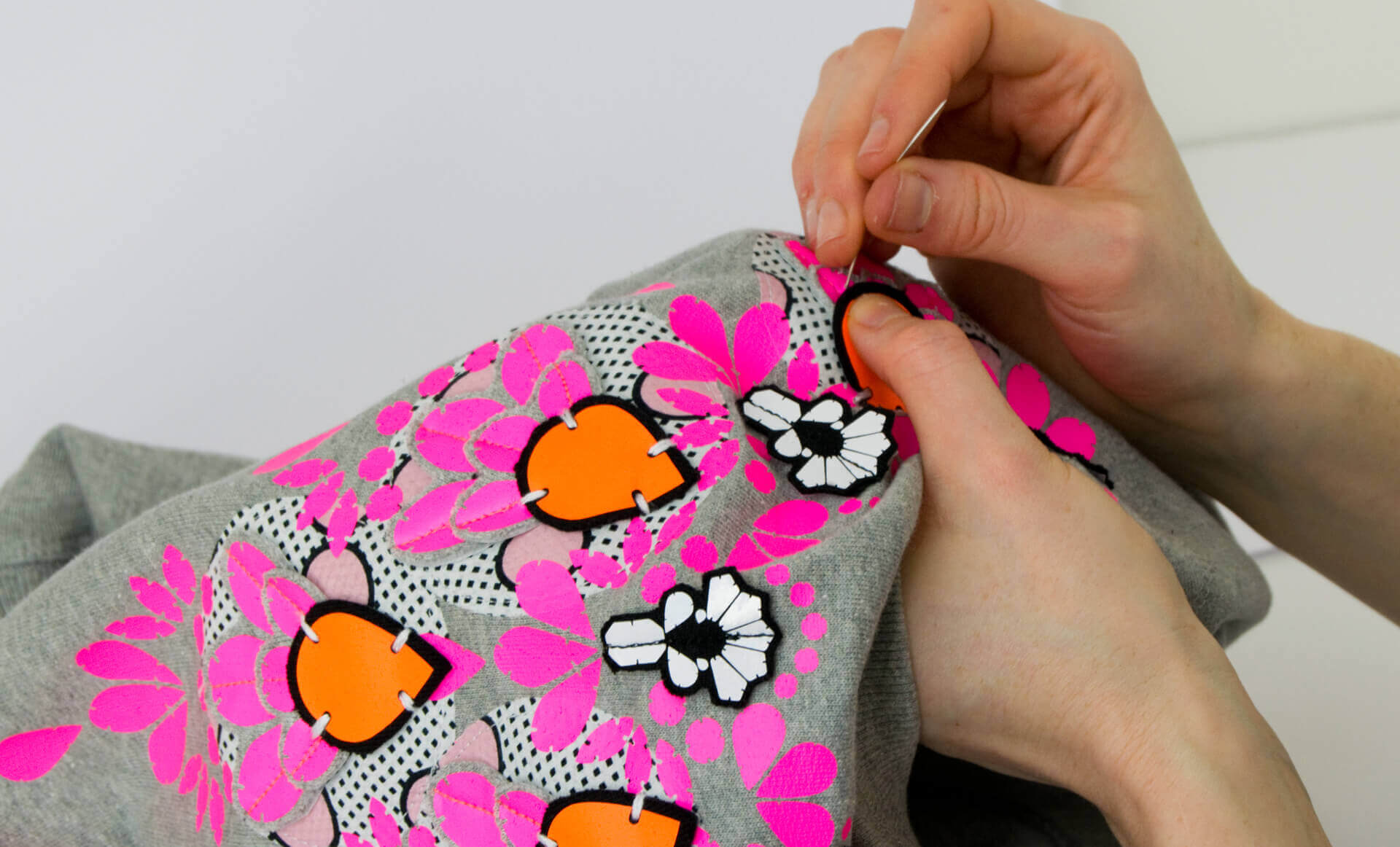 Close up of Bec's hands stitching an orange printed shape to an embellished sweatshirt