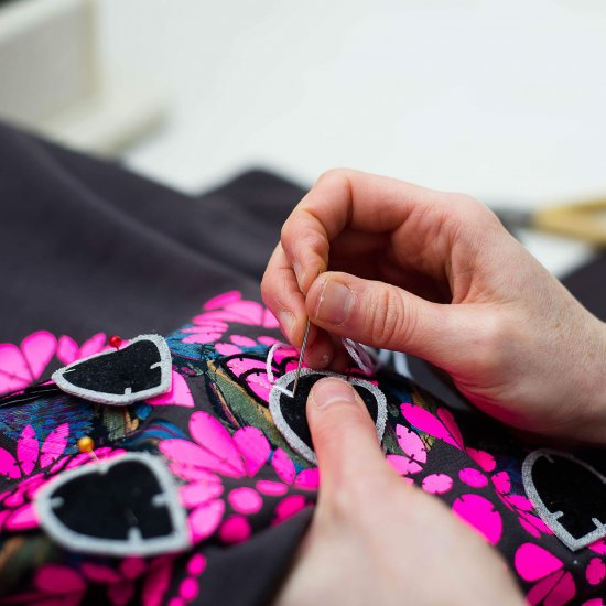 Close up photograph of hands sewing a neon pink embellished sweatshirt