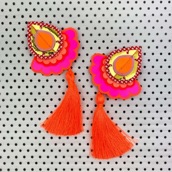fluorescent tassel earrings on a polka dot background