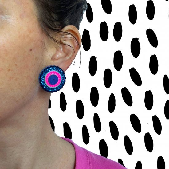 oversize stud earrings in glittery blue and pink, worn by a woman in a pink jumper, sgainst a black and white patterned backgroung