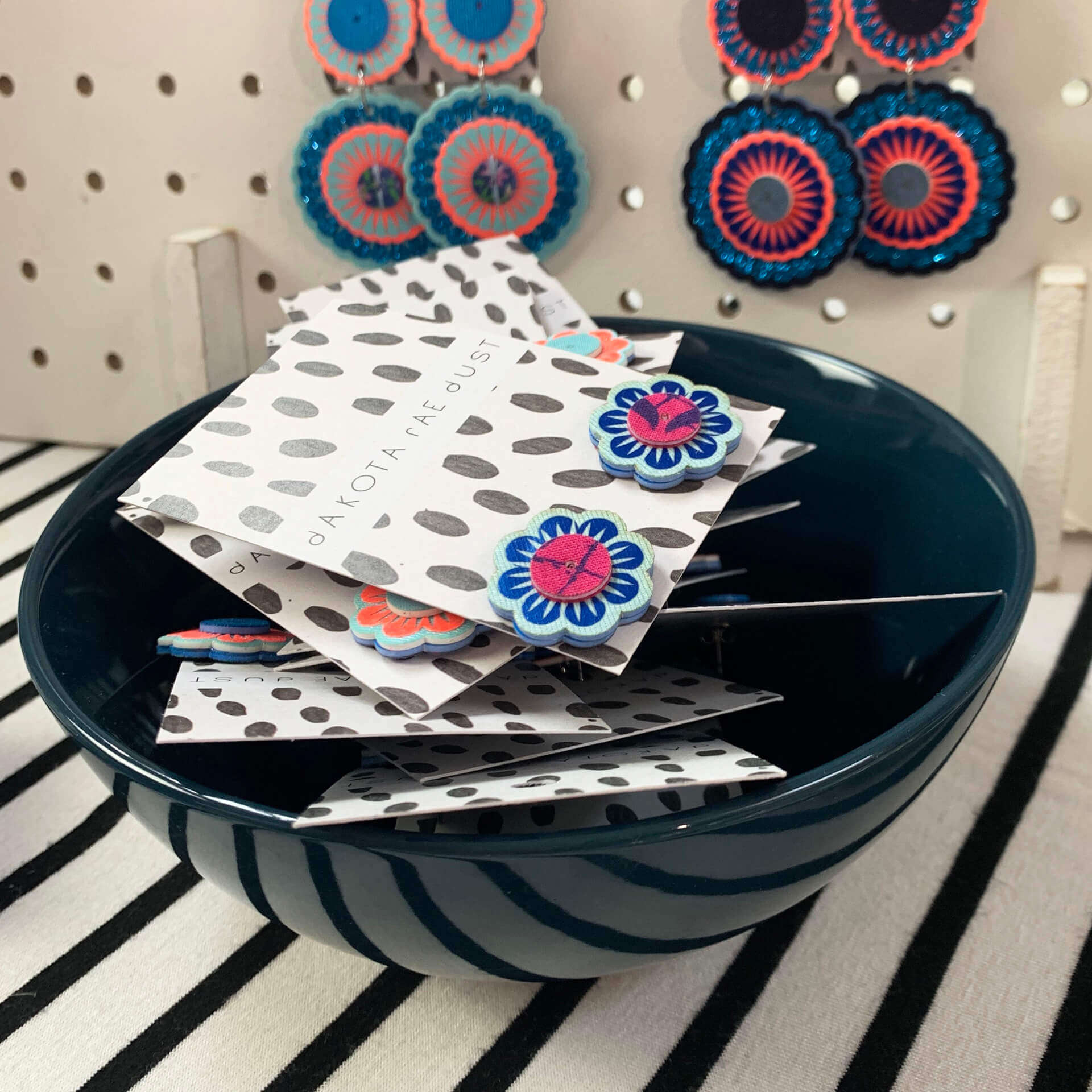 A black bowl filled with colourful flower shaped stud earrings, backed on patterned cards