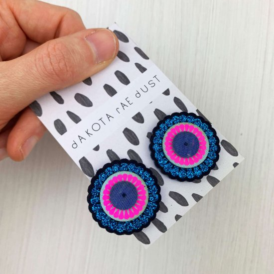 Oversize stud earrings in bright blue glittery and fluorescent pink, on a black and white patterned backing card, held in a hand over a textured white backdrop.