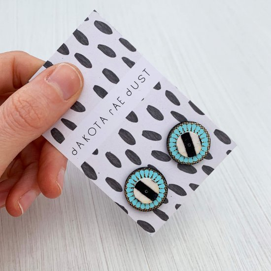 Small circular studs on a monochrome patterned backing card held against a clean white background.