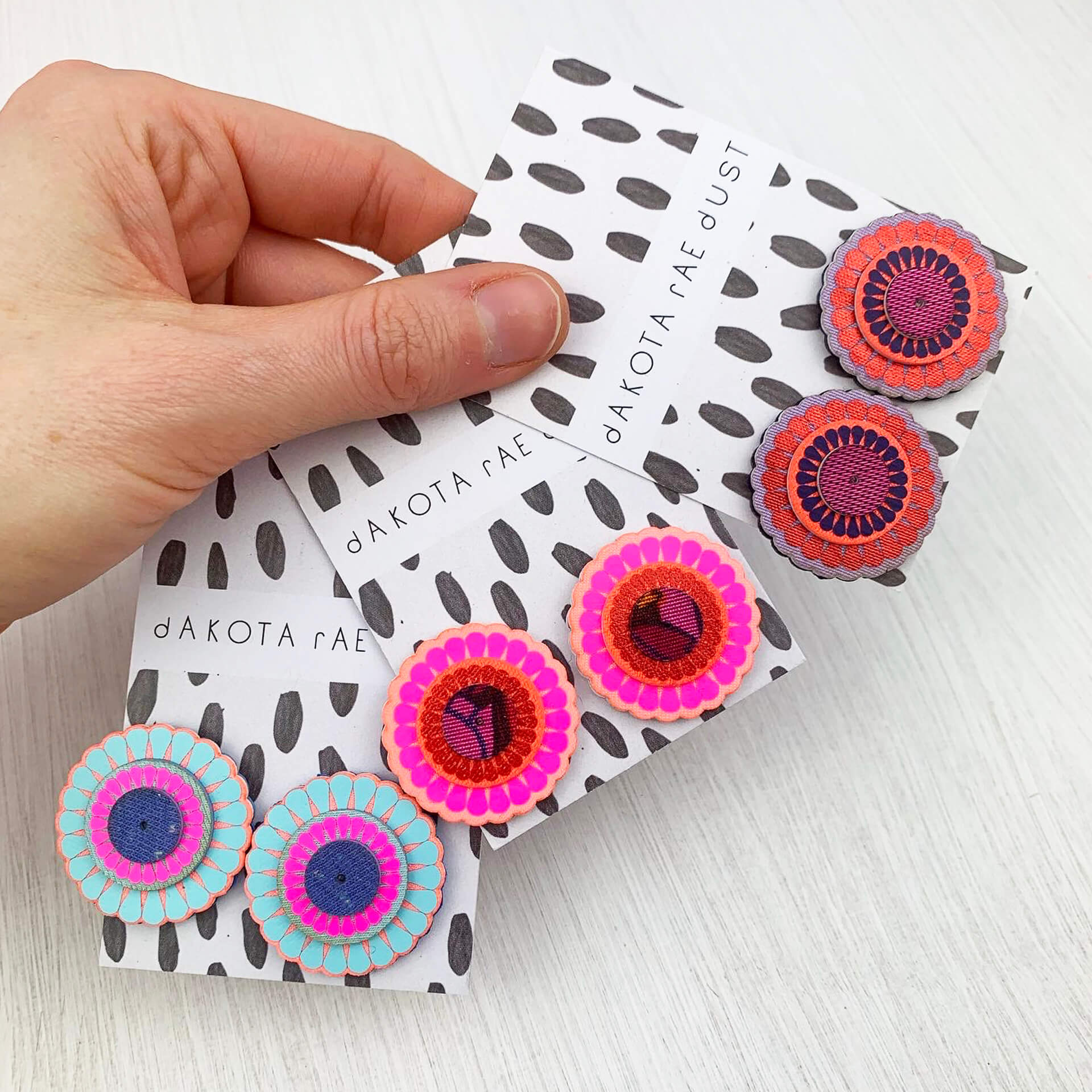 Three pairs of oversize stud earrings held in a woman's hand against a white background. Each colourful, circular pairs of studs is displayed on a black and white patterned backing card, branded with the dakota rae dust logo.