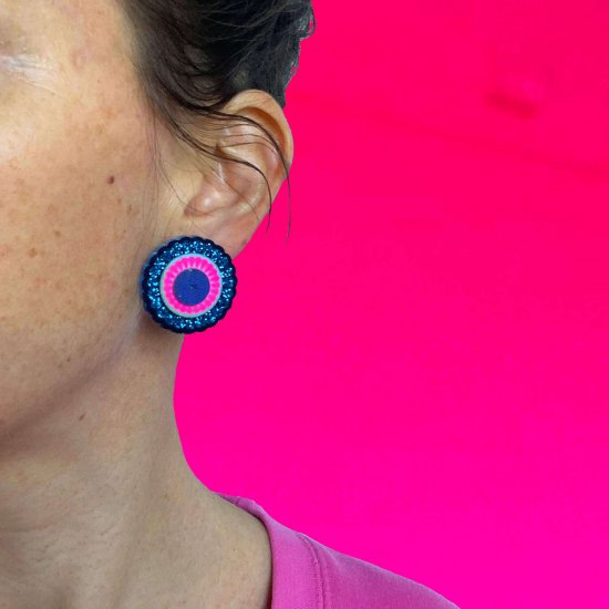 A close up on a circular gittery blue and neon pink stud earring, worn by a woman in a pink sweatshirt against a bright pink backdrop.