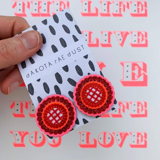A pair of red ornate and oversize studs featuring glittery red detail and red and white fabric laser cut 'sequins', backed on a dakota rae dust branded card are held in a woman's hand in front of a white background printed with fluorescent red printed text