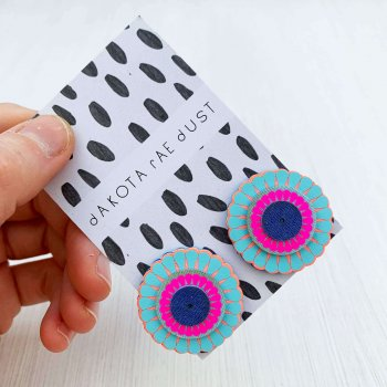 A colourful pair of circular, ornate oversize studs in blue, peach and neon pink, made of tiers of laser cut and vinyl printed discs are seen mounted on a monochrome patterned dakota rae dust branded card, held in a woman's hand. only the fingers and thumb are visible.