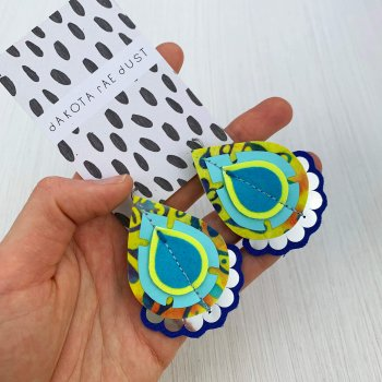 A pair of yellow and blue teardrop shaped colourful earrings are held in a woman's hand against a white textured background. The earrings are displayed on a black and white patterned card.