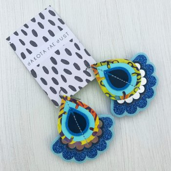A pair of blue and yellow teardrop shaped oversize earrings with a scallop edges frill are displayed on a black and white patterned card against a white background