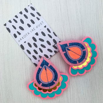 A pair of decorative teardrop shaped, oversize earrings in pink, turquoise and gold mounted on a black and white patterned dakota rae dust branded card, photographed against an off white background