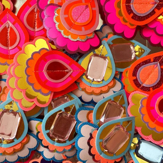 The image is filled with a collection of red, pink, gold and blue statement earrings. They are all teardrop shaped and cut from bold coloured fabric.