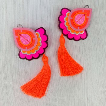 A pair of neon pink, bright orange and purple statement tassel earrings photographed against a plain off white background