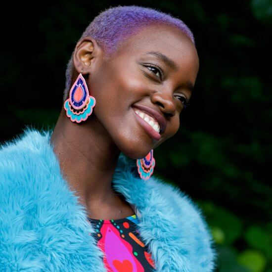 A young black woman with cropped lilac hair wears a pair of colourful, oversize statement earrings by dakota rae dust and a bright blue faux fur wrap. She is smiling and looking past the camera.
