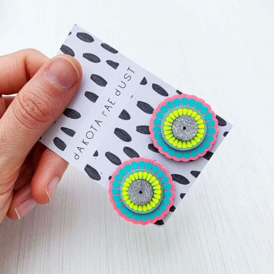 A pair of colourful ornately patterned, oversize studs, backed on a black and white patterned swing tag, printed with a dakota rae dust logo are held in a woman's hand. Only the thumb and fingers are visible. The background is plain off white. The studs are circle shapes in turquoise, pink and yellow.