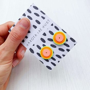 A pair of small stud earrings in zingy fluorescent yellow and orange, backed on a black and white patterned, dakota rae dust branded card are held by a woman's hand against an off white background.