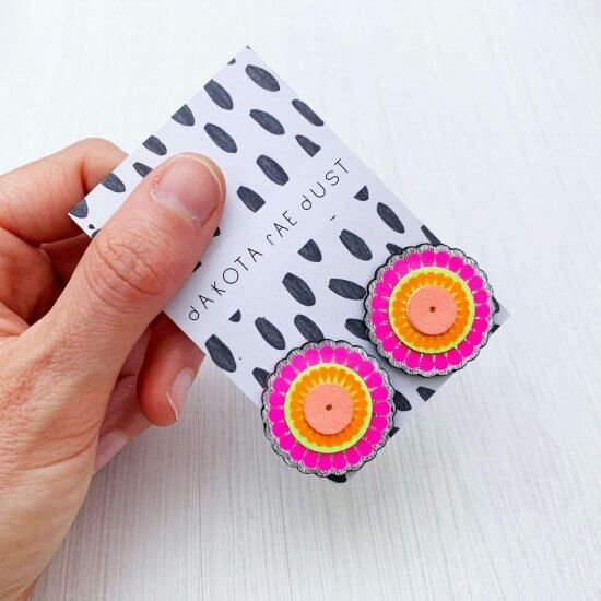Bright pink and orange, colourful oversize studs, mounted on a black and white patterned swing tag, printed with the dakota rae dust logo. The earrings are held in a hand over an off white background. only the thumb and fingers are visible.