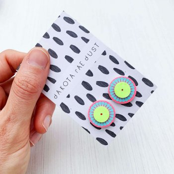Bright pink blue and lime green, small stud earrings, mounted on a black and white patterned swing tag, printed with the dakota rae dust logo. The earrings are held in a hand over an off white background. only the thumb and fingers are visible.